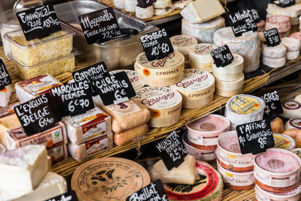 Different cheeses on the counter of a small store at the market. Paris, France stock photo