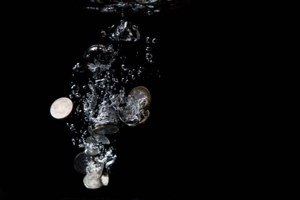 Different coins splashing in water. stock photo