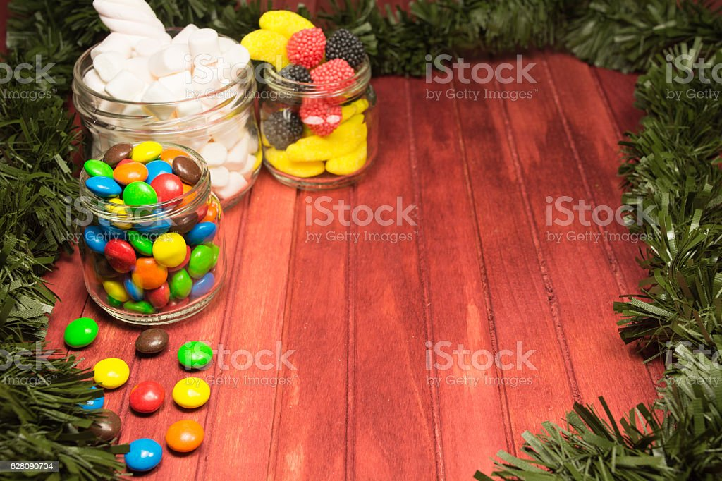 Different color candies on wooden background with green tinsel stock photo