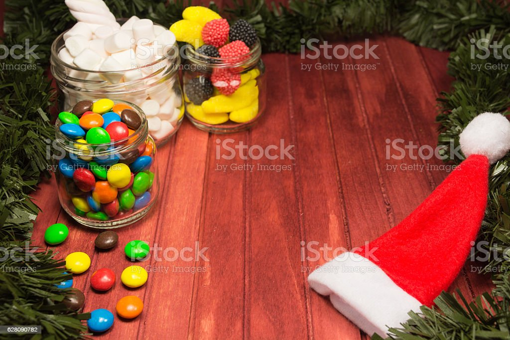 Different color candies on wooden background with tinsel and hat stock photo