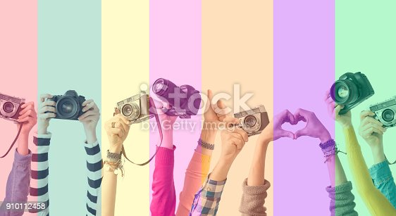 Different color hands and cameras also colorful background