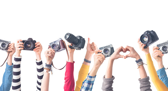 Different color hands holding  cameras