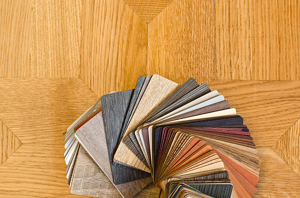 Different color samples of wood floor on brown parquet background. stock photo