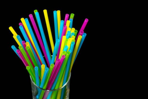 0613 verschiedene farbige Plastik Trinkhalme in ein Glas schwarz background.jpg platziert – Foto
