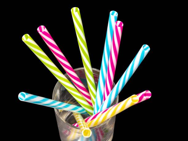 0614 verschiedene farbige Plastik Trinkhalme in ein Glas schwarz background.jpg platziert – Foto