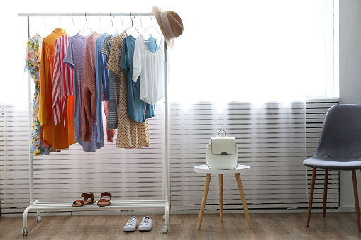 Different colorful casual clothing hanging in row.
