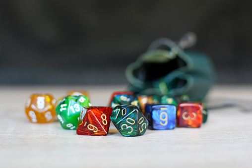 Different colorful role playing dice on table with blurry storage leather bag in backgorund