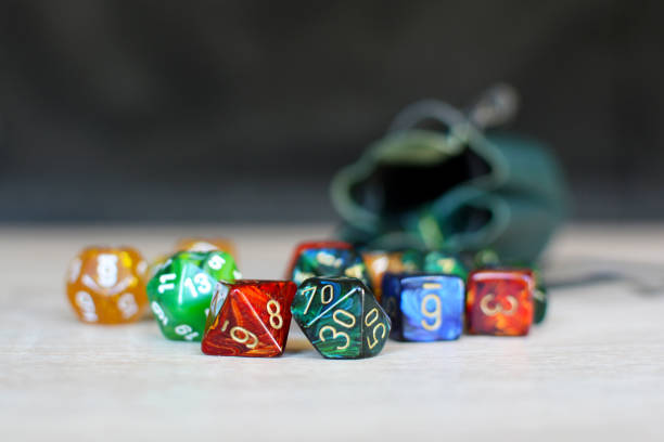 different colorful role playing dice on table with blurry storage leather bag in backgorund - gioco dei dadi foto e immagini stock