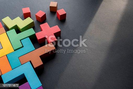 istock Different colorful shapes wooden blocks on black background, flat lay. Geometric shapes in different colors, top view. Concept of creative, logical thinking or problem solving. Copy space 1017311672