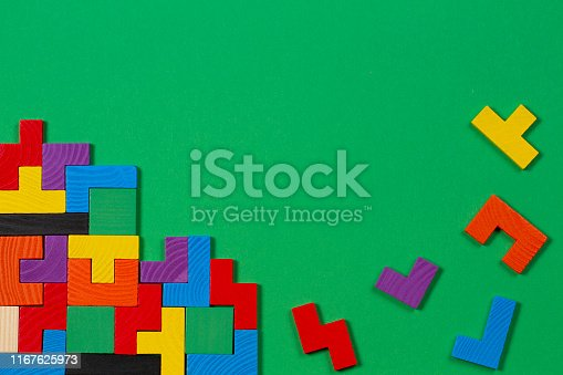 istock Different colorful shapes wooden blocks on green background. Top view 1167625973