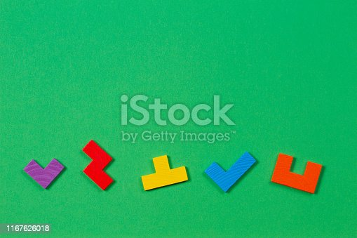 istock Different colorful shapes wooden blocks on green background. Top view 1167626018
