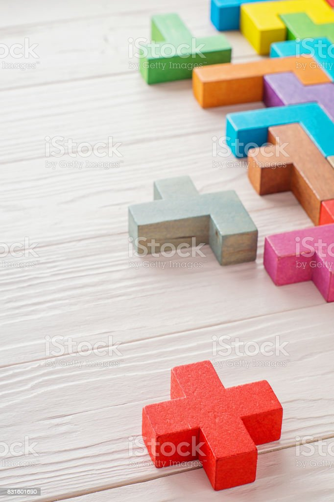 Different colorful shapes wooden blocks on wooden background. stock photo