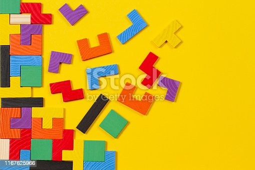 istock Different colorful shapes wooden blocks on yellow background. Top view 1167625966