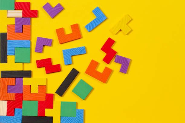 Verschiedene bunte Formen Holzblöcke auf gelbem Hintergrund. Ansicht von oben – Foto