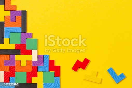 istock Different colorful shapes wooden blocks on yellow background. Top view 1167625993