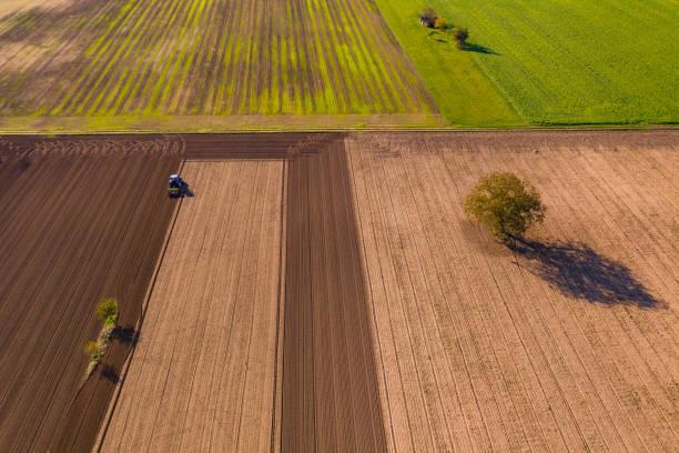 verschiedene farben von feldern und ackerland mit einem traktor sowie verschiedene bäume und blühstreifen - aerial view soil germany stock-fotos und bilder