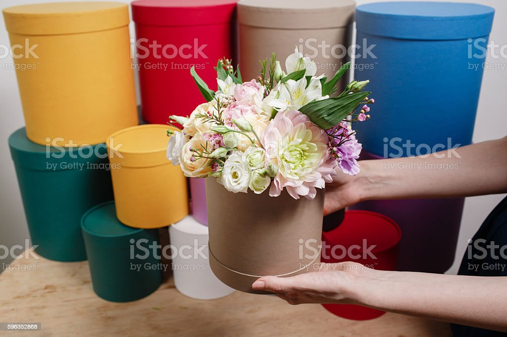 different colors.. Work florist, bouquet in a round box. smelling royalty-free stock photo