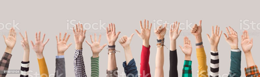 Different colour arms up on gray background stock photo