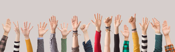 andere kleur armen omhoog op grijze achtergrond - voting hands stockfoto's en -beelden