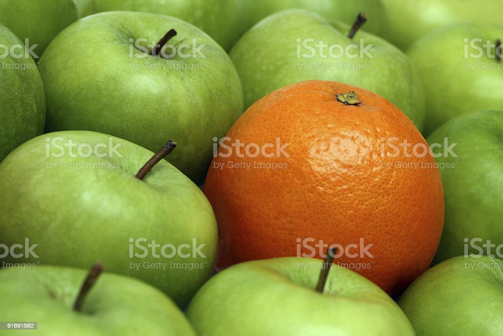 different concepts - orange between apples stock photo