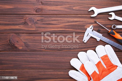 istock Different construction tools on brown wooden background with copy space. 1149116676