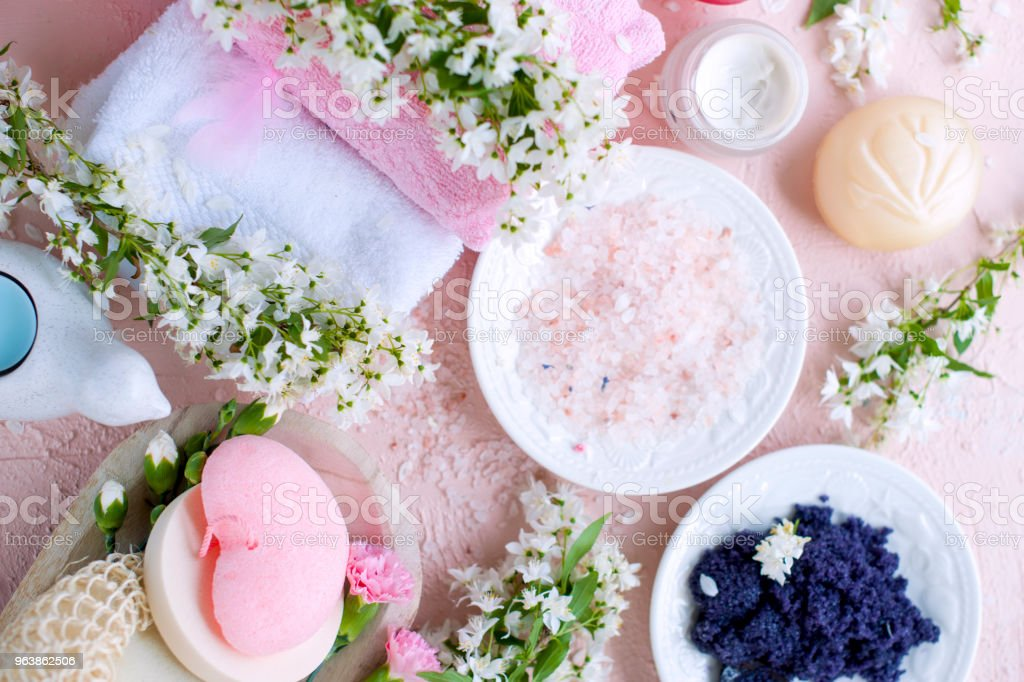 SPA. Different cosmetics for care and beauty. Pink background and flowers. Place for text. Sea salt - Royalty-free Archival Stock Photo