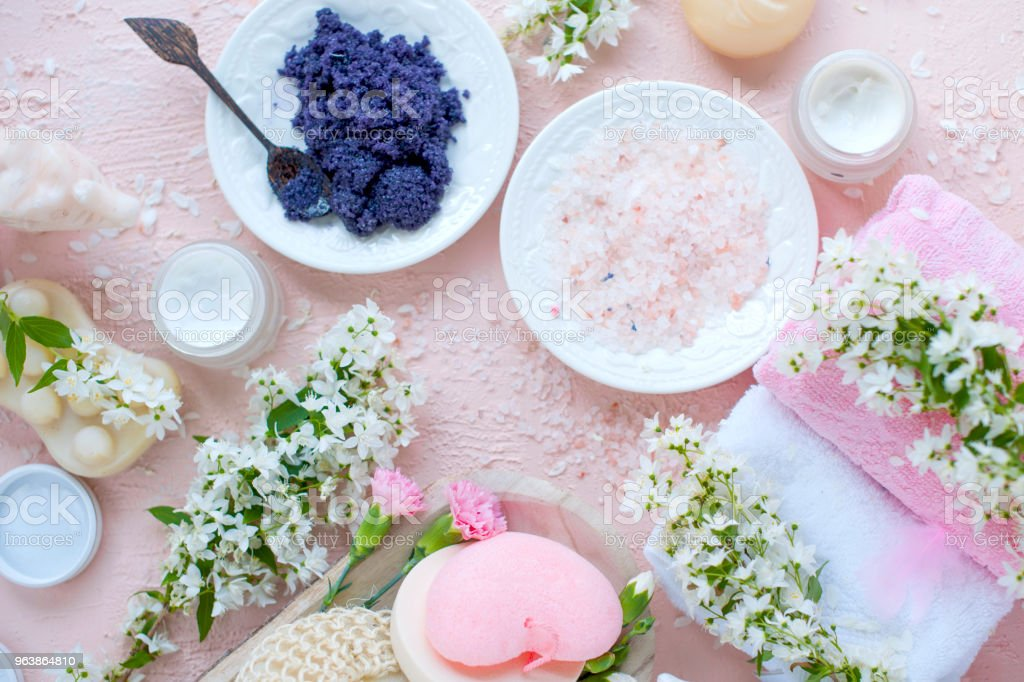 SPA. Different cosmetics for care and beauty. Pink background and white flowers. Place for text. Sea salt, - Royalty-free Archival Stock Photo