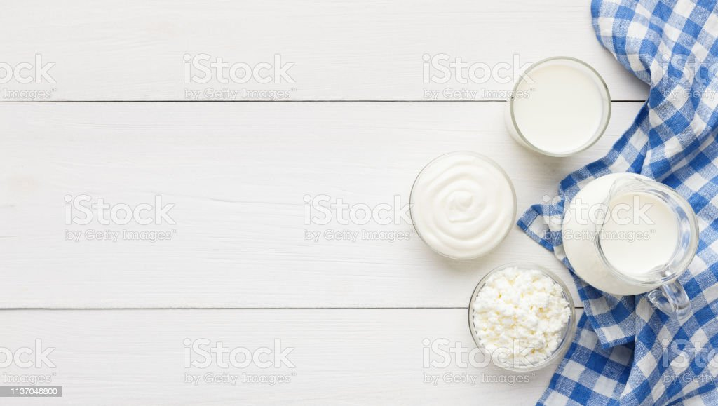 Different dairy products on white wooden background, top view, copy...