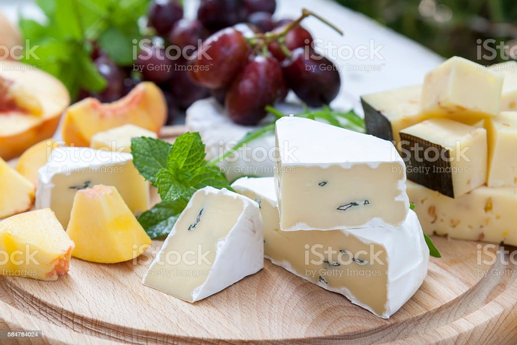 Different delicious cheeses and fruits on wooden round board stock photo