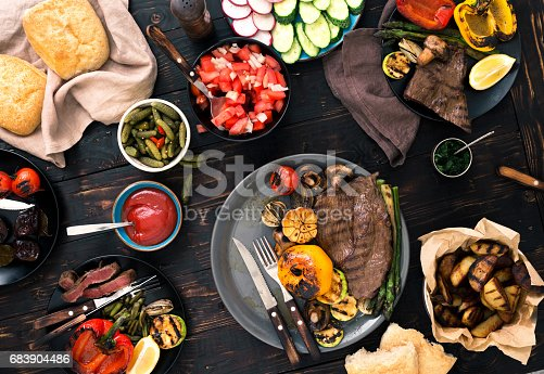 657146780istockphoto Different dishes cooked on the grill, grilled steak and grilled vegetables on the wooden table 683904486