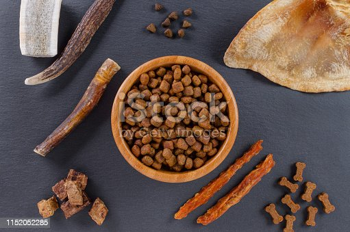 istock different dog food and snack, chicken filet, antlers, lung, ear on black background, top view 1152052285