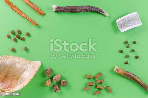 istock different dog food and snack, chicken filet, antlers, lung, ear on green background 1155925649