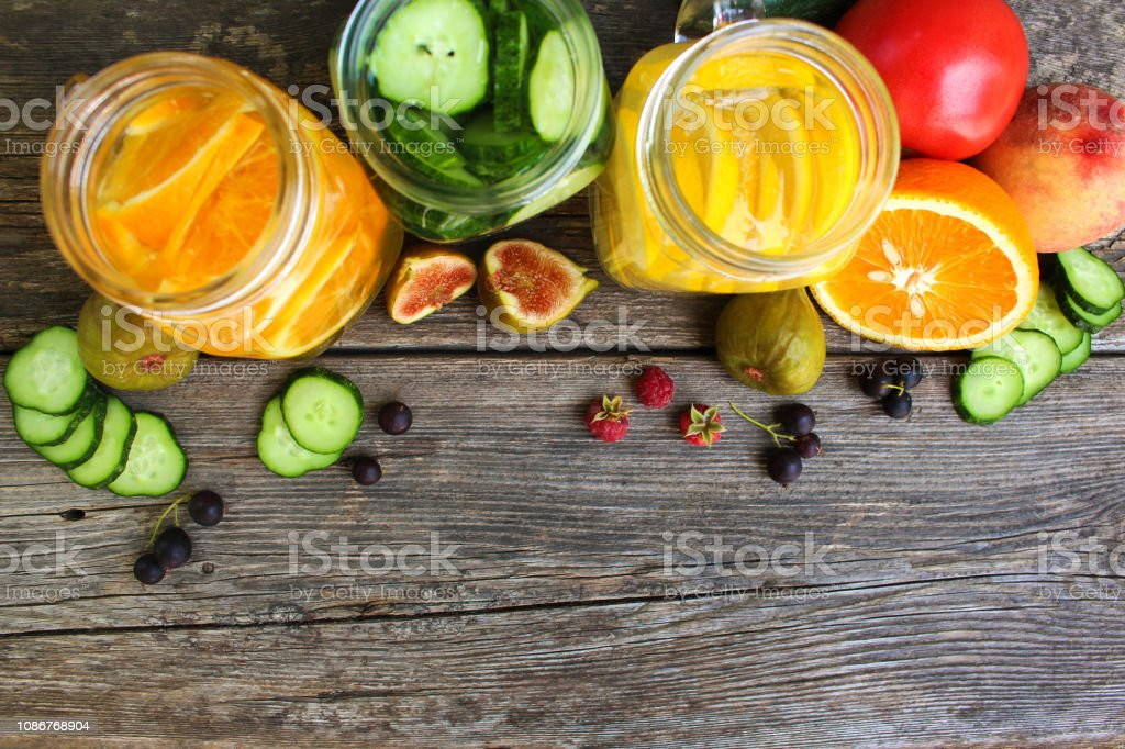 Different drinks, fruits and vegetables on wooden background. stock photo