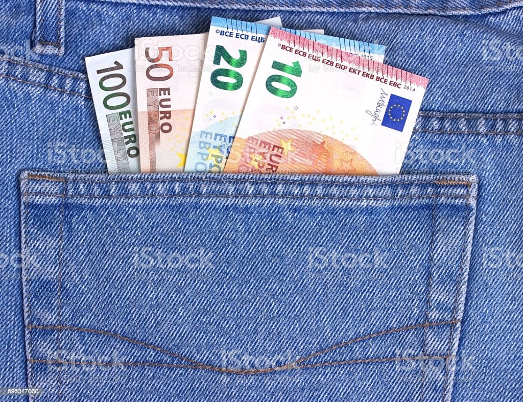 Different Euros bills in blue jeans pocket. stock photo