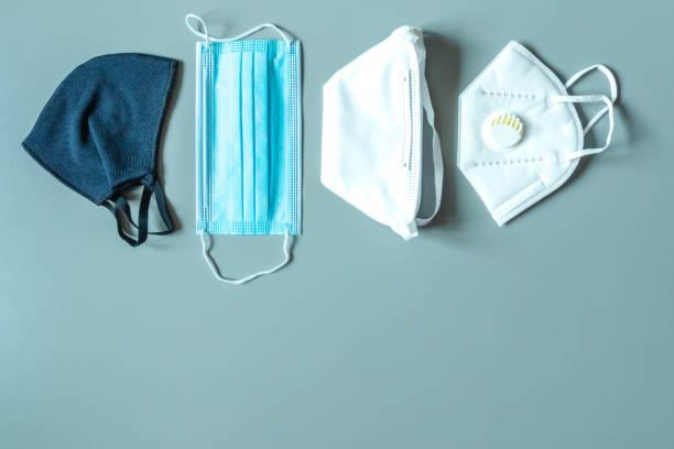 verschiedene gesichtsmasken und atemschutzgerät auf blauem hintergrund. schutz vor viren - luftventil stock-fotos und bilder