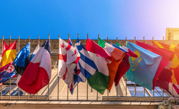 Different flags of many countries on building facade, sky background. Bottom view Different flags of many countries on building facade, sky background. Bottom view citizenship stock pictures, royalty-free photos & images