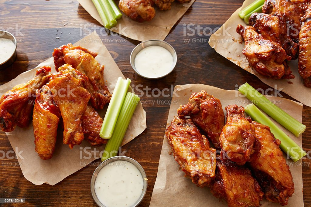 different flavored chicken wings on wooden table stock photo