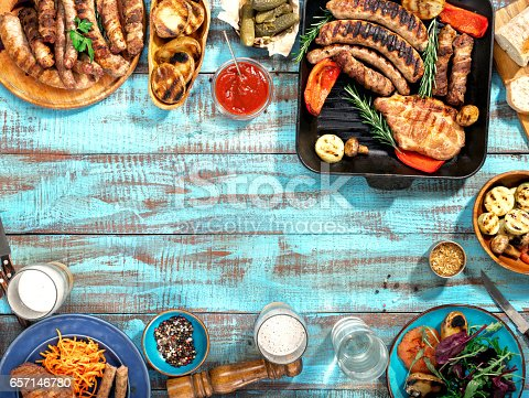 istock Different food cooked on the grill on the blue wooden table on a sunny day, grilled steak, grilled sausage, grilled vegetables and lager beer 657146780
