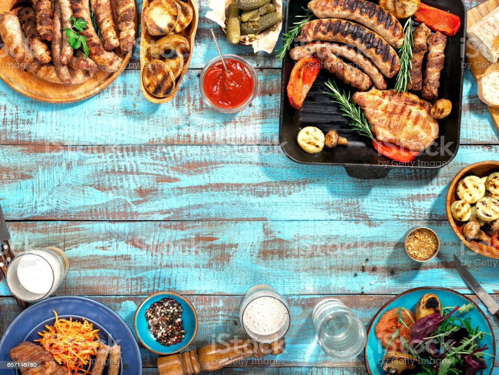 Different food cooked on the grill on the blue wooden table on a sunny day, grilled steak, grilled sausage, grilled vegetables and lager beer - foto de stock