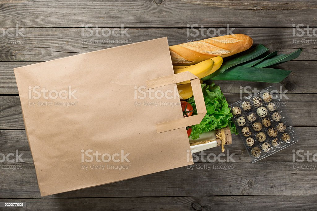Different food in paper bag on wooden background zbiór zdjęć royalty-free
