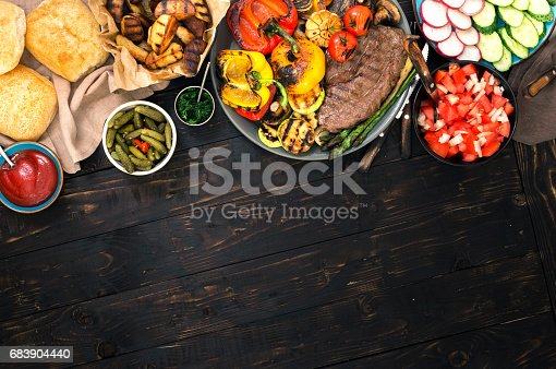 690274036 istock photo Different foods cooked on the grill, grilled steak and grilled vegetables on the wooden table with border 683904440