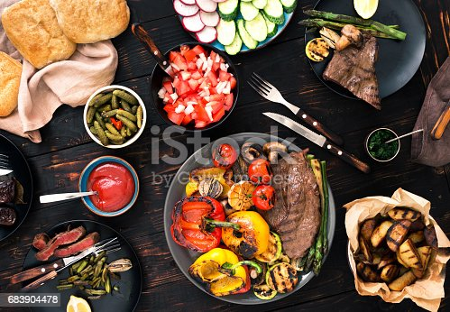 657146780istockphoto Different foods cooked on the grill on the wooden table, grilled steak and grilled vegetables 683904478
