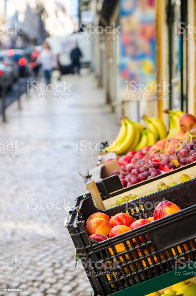 Different fruits in baskets in front of store stock photo