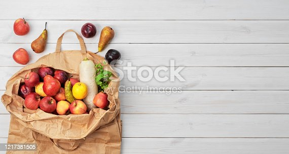 1126188273 istock photo Different fruits , vegetables in paper bag on wooden background, copy space, flat lay. Grocery shopping concept, zero waste. Package-free food shopping, eco friendly natural bag with organic products. 1217381505
