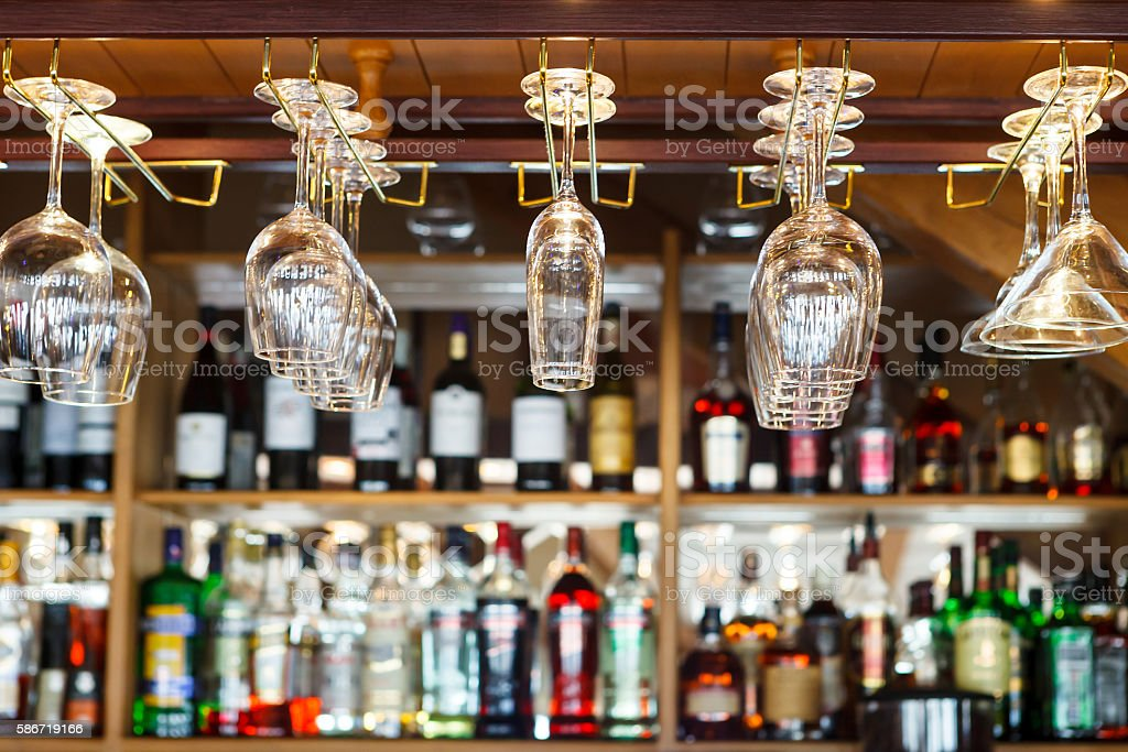 different glasses hanging over the bar. Soft focus. - foto de acervo