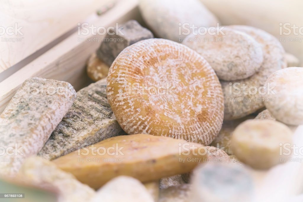 Different grades of appetizing delicacy aged cheese with mold in wooden box. Gastronomic dainty dairy produce on market counter, real scene, food market stock photo