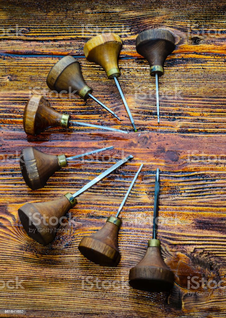 Different gravers for jewelry on wooden background stock photo
