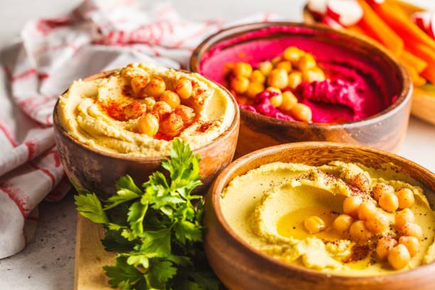 Different hummus bowls. Chickpea hummus, avocado hummus and beetroot hummus. stock photo
