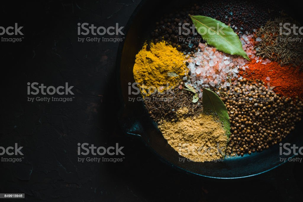 Different Indian spices  in pan on dark background top view stock photo