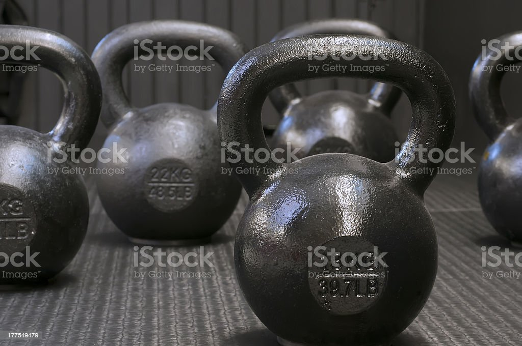 Different kettlebell weights on carpet floor Kettlebells on gym floor Bell Stock Photo